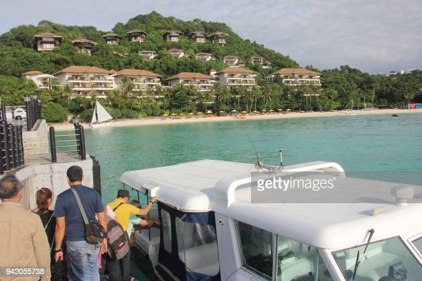 In this photo taken on January 15 tourists board a speedboat near a forestland area on Boracay island in Malay town Aklan province central...