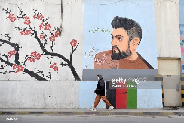 In this photo taken on January 19 a man walks past a barrier wall painted with an image of former Afghan Tolo TV presenter Yama Siawash, who was...