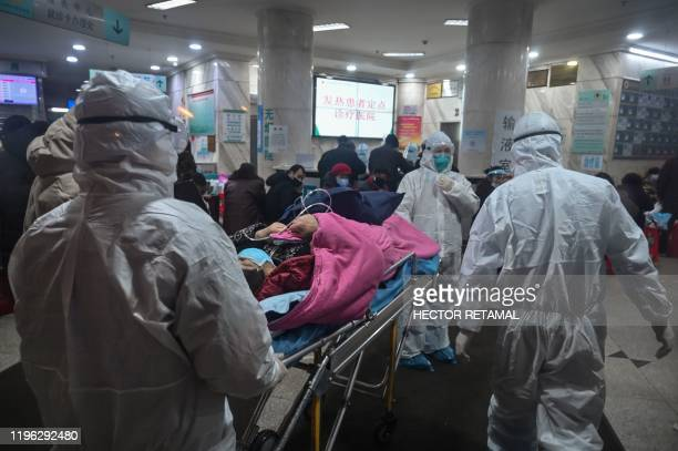 In this photo taken on January 25 medical staff wearing protective clothing to protect against a previously unknown coronavirus arrive with a patient...