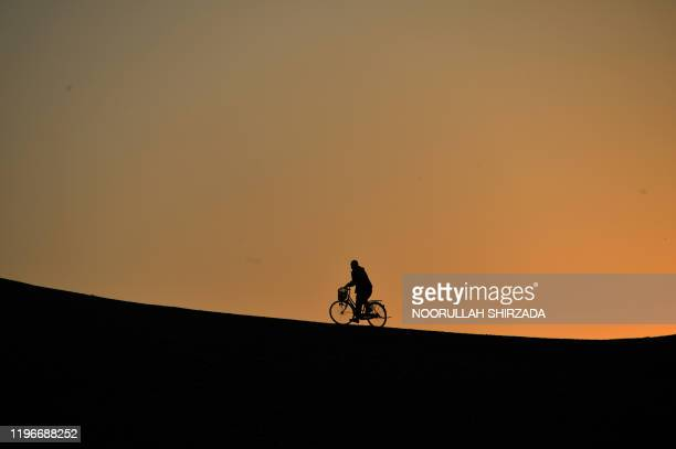 In this photo taken on January 26 a man rides a bicycle to a hilltop during sunset in Jalalabad.