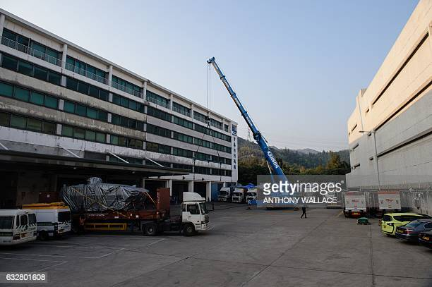 In this photo taken on January 26 a worker walks past impounded tarpaulincovered armoured troop carrier Terrex vehicles belonging to the Singapore...