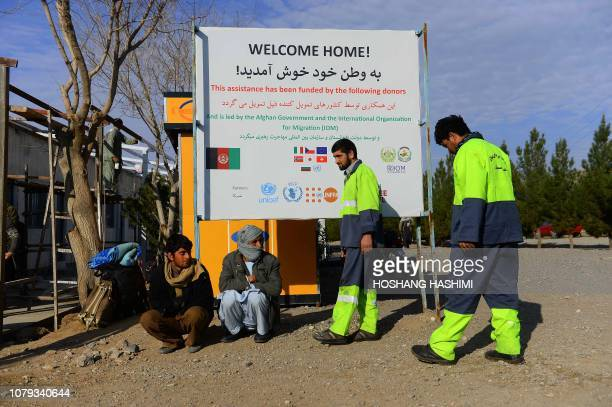 In this photo taken on January 3 Afghan returnees sit under an International Organization for Migration transit centre sign after arriving from Iran...
