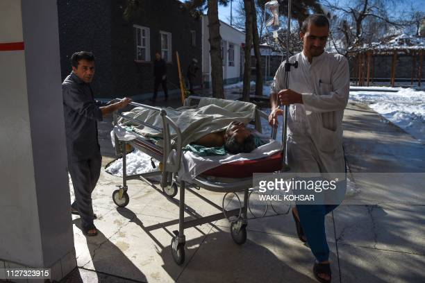In this photo taken on January 5 Afghan medical staff members transport an injured man on a stretcher at the Surgical Centre for War Victims run by...