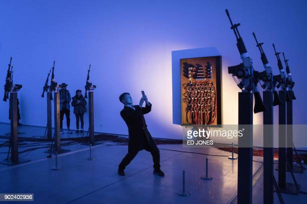 In this photo taken on January 8, 2018 a man takes a photo at an exhibition entitled 'Mirror Organs: Play of Metonymy' by South Korean artist Kelvin...