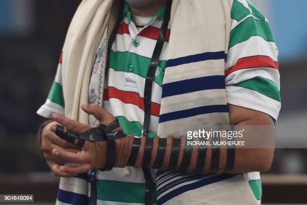 In this photo taken on January 9 a member of the Indian Jewish community binds the tefillin on his hand before a morning prayer service at the Magen...