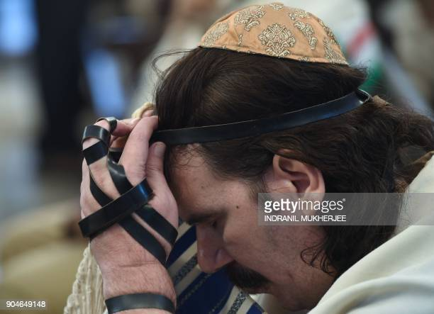 In this photo taken on January 9 a member of the Indian Jewish community touches the tefillin on his forehead during a morning prayer service at the...