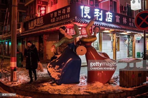 In this photo taken on January 9 a woman walks past a statue of North Korean women dancing and playing drums in the market place in the border city...