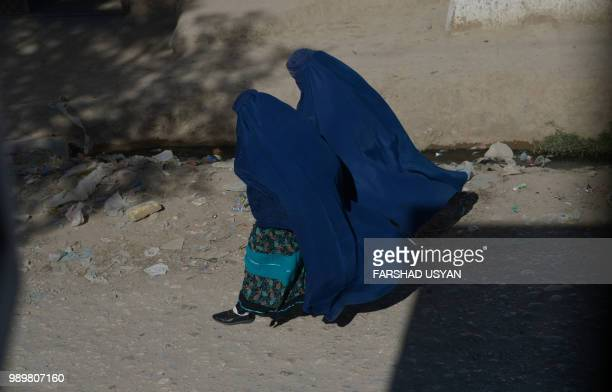 In this photo taken on July 1 Afghan burqaclad women walk along a street on the outskirts of MazariSharif