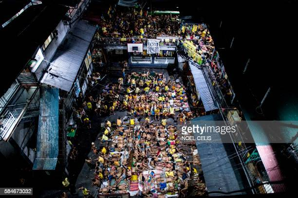 TOPSHOT In this photo taken on July 21 2016 inmates sleep on the ground of an open basketball court inside the Quezon City jail at night in Manila...