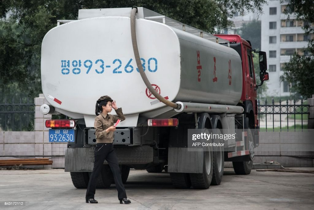 In this photo taken on July 21, 2017, a petrol station worker walks past a fuel truck in Pyongyang. Top of the list for new sanctions on North Korea after its sixth nuclear test is an oil embargo, which analysts say would have a crippling effect on the wider economy -- but might do little to curb its weapons programmes. / AFP PHOTO / Ed JONES