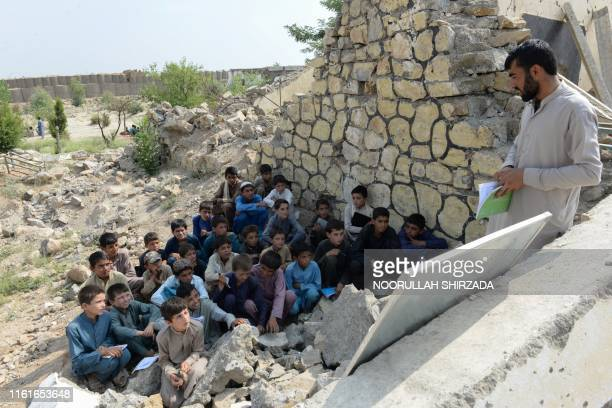In this photo taken on July 22 Afghan schoolchildren study at the destroyed Papen High School in Deh Bala district of Nangarhar province. - The US...