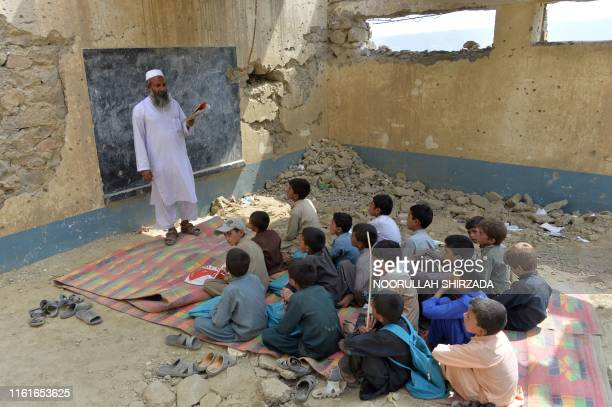 In this photo taken on July 25 Afghan schoolchildren study at the destroyed Papen High School in Deh Bala district of Nangarhar province. - The US...