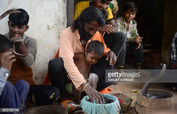 In this photo taken on July 25 an Indian snake charmer trains his son with the handling of a cobra snake in Kapari village around 40km southwest of...