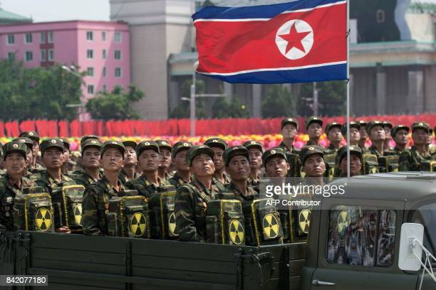 In this photo taken on July 27 Korean People's Army soldiers carrying packs marked with a radioactive symbol take part in a military parade in...