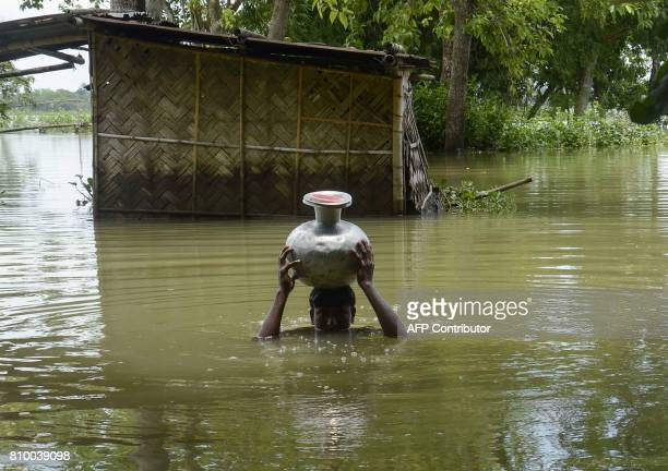 In this photo taken on July 6 an Indian youth carries a container of drinking water through floodwaters in Padderpar village in Karimganj district in...
