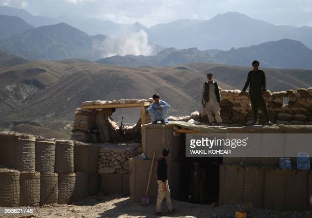 In this photo taken on July 7 Afghan Local Police officials look on as smoke rises after an air strike bomb on Islamic State militants positions in a...