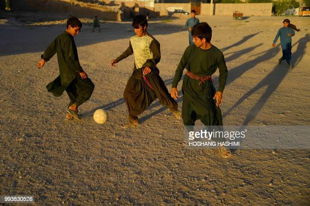 In this photo taken on July 7 Afghan youths play football in field on the outskirts of Herat