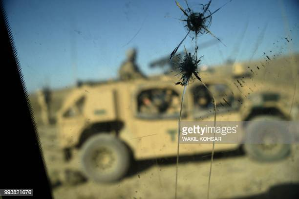 TOPSHOT In this photo taken on July 7 US Army soldiers from NATO are seen through a cracked window of an armed vehicle in a checkpoint during a...