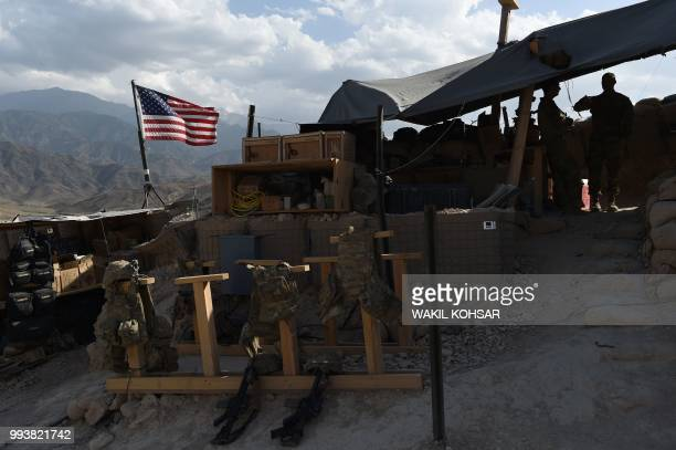 In this photo taken on July 7 US Army soldiers from NATO looks on as U.S. Flag flies in a checkpoint during a patrol against Islamic State militants...