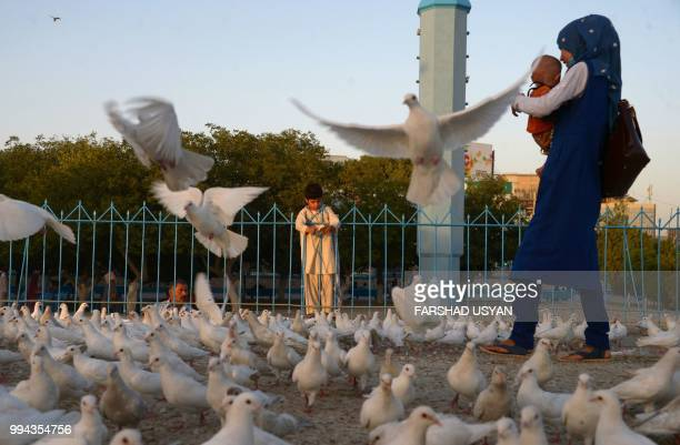 In this photo taken on July 8 2018 an Afghan girl holds a baby as pigeons fly by in the courtyard of HazrateAli shrine or Blue Mosque in MazariSharif