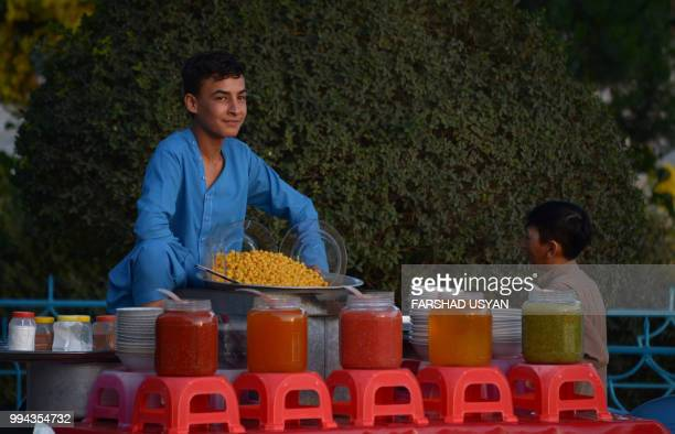In this photo taken on July 8 2018 an Afghan vendor looks on as he sells chickpeas in the courtyard of HazrateAli shrine or Blue Mosque in...