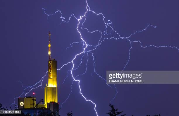 TOPSHOT In this photo taken on June 07 2016 lightnung is seen behind the Commerzbank Tower in Frankfurt western Germany Germany's secondlargest...