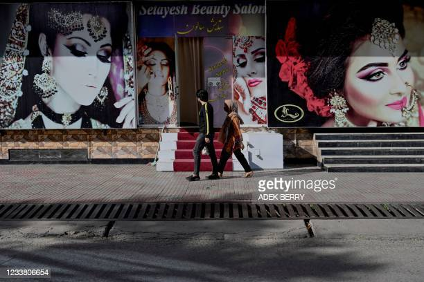 In this photo taken on June 10 a couple walks past a beauty parlour in Kabul. - The Taliban outlawed dozens of seemingly innocuous activities and...