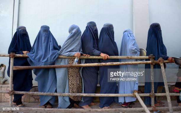 TOPSHOT In this photo taken on June 12 Afghan burqaclad women stands as they wait to receive food donated by a private charity during the Islamic...