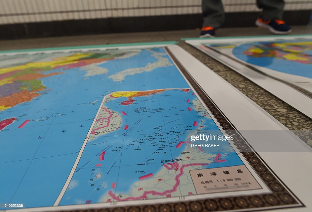 In this photo taken on June 15, 2016 a vendor stands behind a map of China including an insert with red dotted lines showing China's claimed territory in the South China Sea, in Beijing. Chinese pressure was blamed June 16 for a stunning diplomatic U-turn by Southeast Asian Nations that saw them retract a statement sounding alarm over Beijing's island building in the South China Sea. China claims nearly all of the South China Sea -- a vast tract of water through which a huge chunk of global shipping passes. The Philippines, Taiwan, Brunei, Malaysia and Vietnam have competing claims to parts of the sea, which is believed to harbour significant oil and gas deposits. / AFP / GREG