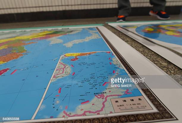 In this photo taken on June 15 2016 a vendor stands behind a map of China including an insert with red dotted lines showing China's claimed territory...