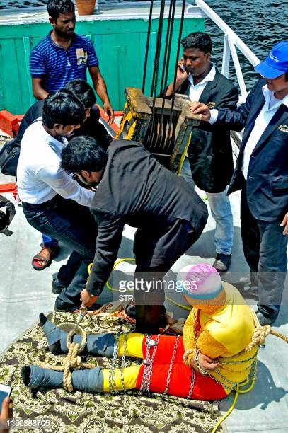 In this photo taken on June 16 2019 Indian stuntman Chanchal Lahiri known by his stage name Jadugar Mandrake is prepared for being lowered into the...
