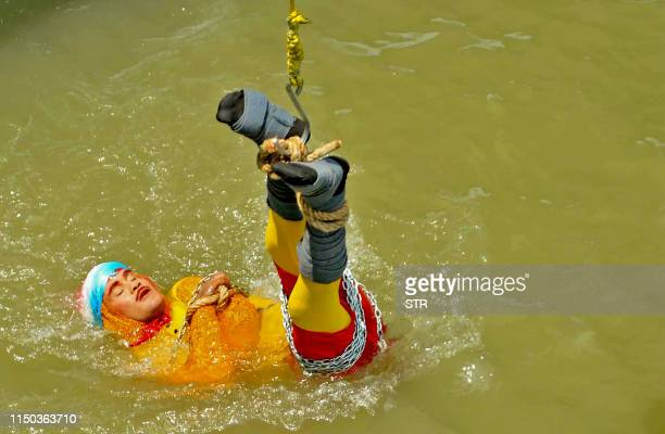 In this photo taken on June 16 2019 Indian stuntman Chanchal Lahiri known by his stage name Jadugar Mandrake is lowered into the Ganges river while...