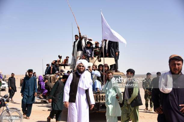 In this photo taken on June 17 Afghan Taliban militants and residents stand on a armoured Humvee vehicle of the Afghan National Army as they...