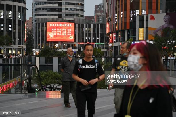 """In this photo taken on June 2 a large screen shows a propaganda slogan which reads """"Socialist core values; prosperity, democracy, civility, harmony,..."""