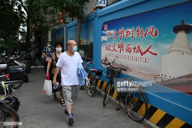 """In this photo taken on June 2 a man walks past a propaganda slogan which reads """"Be civilised, establish the new trend"""", on the wall of a construction..."""