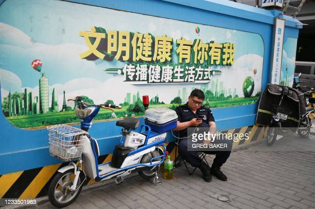 """In this photo taken on June 2 a security guard sits in front of a propaganda slogan which reads """"Civilisation and Health; You and Me; Spread the..."""