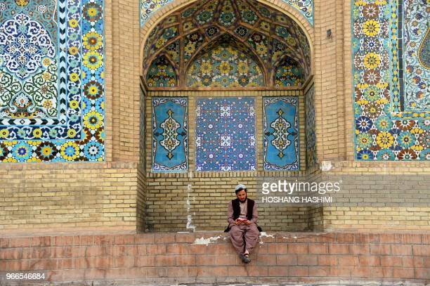 TOPSHOT In this photo taken on June 2 an Afghan Muslim reads the Quran outside a mosque during the holy month of Ramadan in Herat Province Muslims...