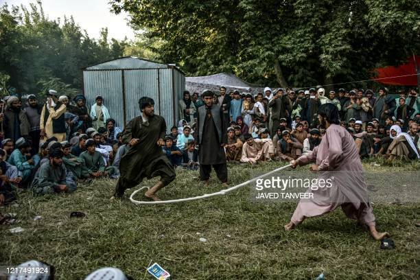 In this photo taken on June 2 men crowd to watch people playing a traditional rope game called Dora in a field despite the spread of the COVID19...
