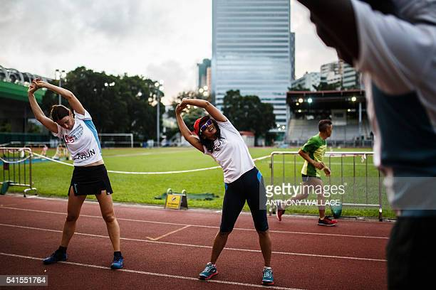 In this photo taken on June 2 Naina who has been in Hong Kong for 12 years after fleeing violence in her community in South Asia leads a warm up...