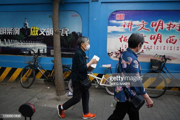 """In this photo taken on June 2 two women walk past propaganda slogans which read """"Learn civilised rules; Be a civilised citizen"""" and """"Be civilised,..."""