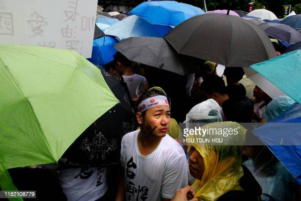 In this photo taken on June 23 protesters gather in the rain during a rally against proChina media in front of the Presidential Office building in...
