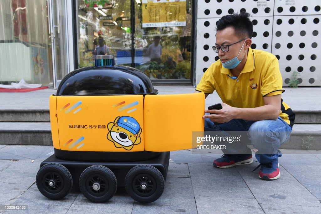In this photo taken on June 28, 2018, a Suning worker loads a delivery robot with groceries outside a Suning supermarket during a demonstration of the robot in Beijing. - Along a quiet residential street on the outer edges of Beijing, a yellow and black cube about the size of a small washing machine trundles leisurely to its destination. This 'little yellow horse' is an autonomous delivery robot, ferrying daily essentials like drinks, fruit and snacks from the local store to the residents of the 'Kafka' compound in the Chinese capital. (Photo by GREG BAKER / AFP) / TO