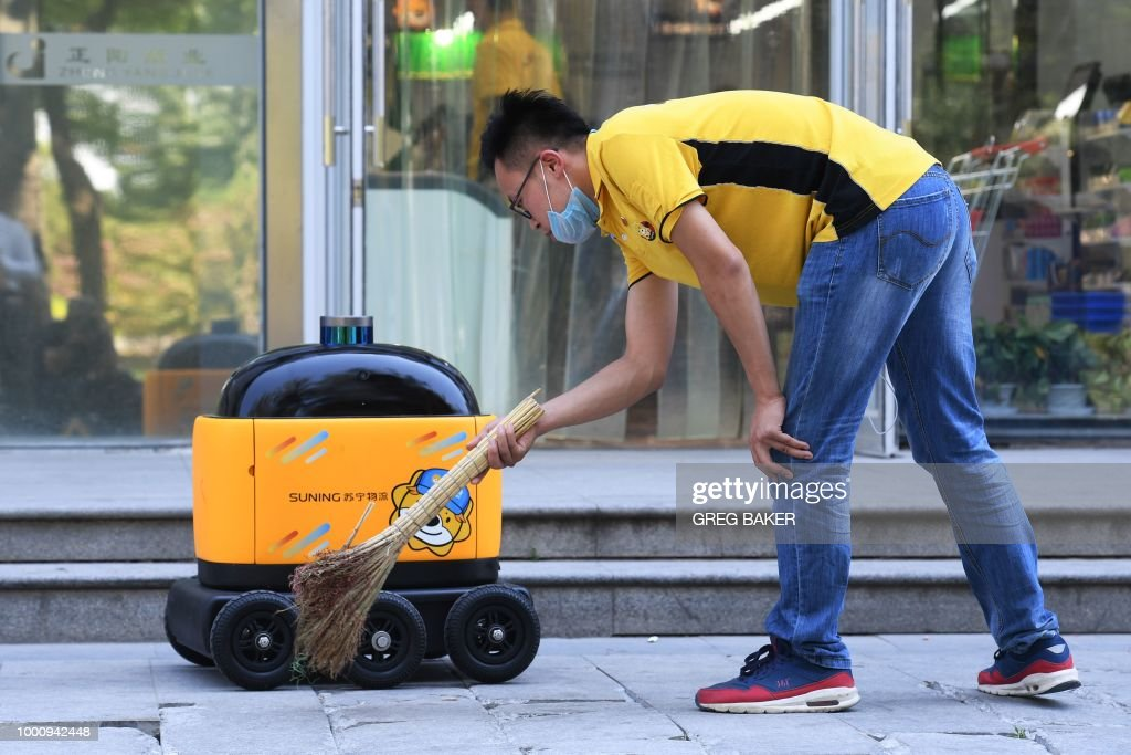 In this photo taken on June 28, 2018, a Suning worker sweeps near a delivery robot outside a Suning supermarket during a demonstration of the robot in Beijing. - Along a quiet residential street on the outer edges of Beijing, a yellow and black cube about the size of a small washing machine trundles leisurely to its destination. This 'little yellow horse' is an autonomous delivery robot, ferrying daily essentials like drinks, fruit and snacks from the local store to the residents of the 'Kafka' compound in the Chinese capital. (Photo by GREG BAKER / AFP) / TO