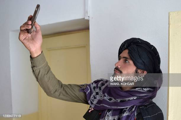 In this photo taken on June 3 a Taliban fighter searches for a network signal for his mobile phone at a hospital in the Andar district of Ghazni...