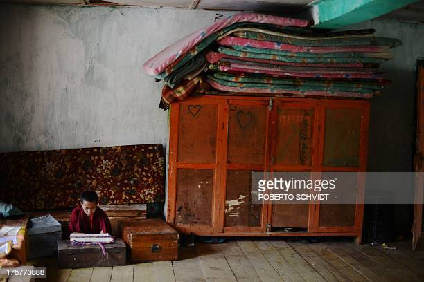 In this photo taken on June 3 a young Buddhist monk studies in a corner of a room that is used as a dormitory and class room at the Dechen Phodrang...