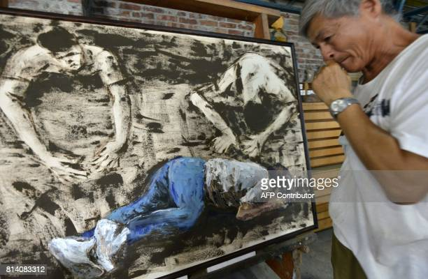In this photo taken on June 30 Taiwan artist and former political prisoner Chen Wujen displays one of his paintings during an interview in Tainan...