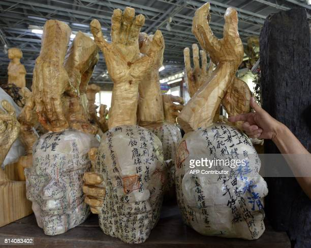 In this photo taken on June 30 Taiwan artist and former political prisoner Chen Wujen points at his sculptures during an interview in Tainan southern...