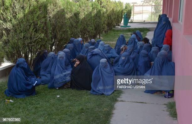 TOPSHOT In this photo taken on June 4 2018 Afghan burqaclad women wait to receive aid by AfghanTurkish school during the holy month of Ramdan in...