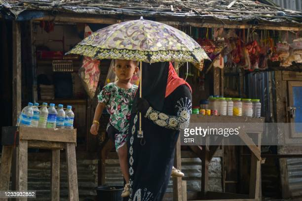 In this photo taken on June 5 a member of the internally displaced Rohingya Muslim community carries a child as she walks through the Thet Kay Pyin...
