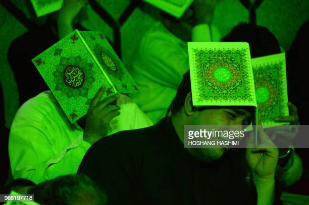 In this photo taken on June 5 Afghan Shiite Muslim worshippers hold holy Quran as they pray during the Laylat alQadr at a mosque in Herat province...